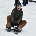 happy teen on sledding hill