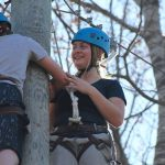 Teen helping another with ropes course