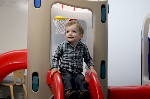 Little boy on slide in toddler room